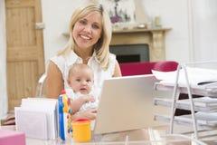 Madre e bambino in Ministero degli Interni con il computer portatile Fotografia Stock