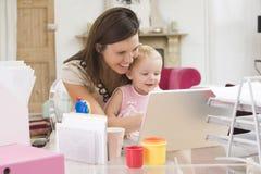 Madre e bambino in Ministero degli Interni con il computer portatile Fotografie Stock Libere da Diritti
