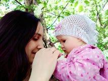 Madre e bambino nei fiori di Apple fotografia stock