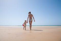 Madre e bambino posteriori con il secchio in spiaggia Immagini Stock Libere da Diritti