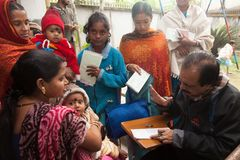 Madre e bambino riuniti nell'all'aperto di una clinica per di sotto previleged fotografia stock