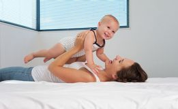 Madre e bambino sorridente sveglio che giocano a letto Immagine Stock Libera da Diritti