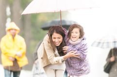 Madre e bambino sotto l'ombrello in tempo piovoso. Fotografia Stock