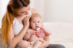Madre e bambino su un letto bianco Mamma e neonata in pannolino che gioca nella camera da letto soleggiata Fotografia Stock