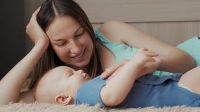 Madre e bambino su un letto bianco Mamma e neonato in pannolino che gioca nella camera da letto soleggiata Genitore e bambino che video d archivio