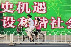 Madre e bambino su una bici che passa un grande tabellone per le affissioni, Pechino, Cina Fotografia Stock