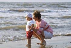 Madre e bambino su una spiaggia Fotografia Stock