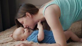 Madre e bambino sul letto Mamma e neonato in pannolino che gioca nella camera da letto soleggiata Genitore e bambino che si rilas stock footage