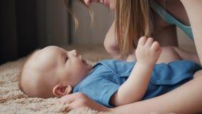 Madre e bambino sul letto Mamma e neonato in pannolino che gioca nella camera da letto soleggiata Genitore e bambino che si rilas archivi video