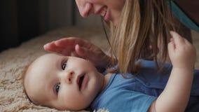 Madre e bambino sul letto Mamma e neonato in pannolino che gioca nella camera da letto soleggiata Genitore e bambino che si rilas video d archivio