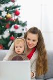 Madre e bambino vicino all'albero di Natale per mezzo del computer portatile Immagine Stock Libera da Diritti