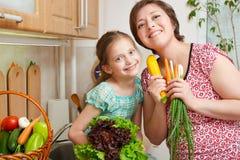 Madre e derivato con le verdure e frutta fresca nell'interno della cucina Genitore e bambino Concetto sano dell'alimento immagini stock