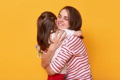 Madre e doughter abbracciarsi con amore, poca gioia sveglia di desideri della ragazza la sua mamma in vacanza, posa sopra lo stud fotografie stock libere da diritti