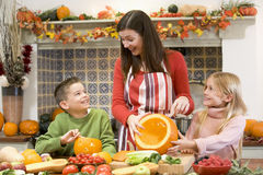 Madre e due bambini che intagliano le zucche immagini stock libere da diritti