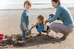 Madre e due bambini sulla spiaggia Immagini Stock