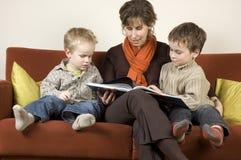 Madre e due figli che leggono un libro 3 Immagini Stock