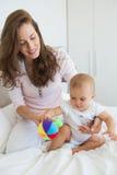 Madre e fare da baby-sitter con il giocattolo sul letto Immagini Stock