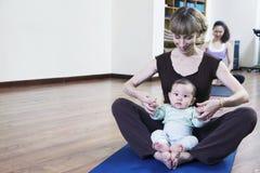 Madre e fare da baby-sitter a gambe accavallate e facendo yoga in una classe di yoga Fotografie Stock Libere da Diritti
