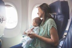 Madre e fare da baby-sitter insieme in aeroplano fotografie stock