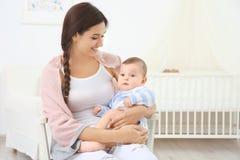 Madre e fare da baby-sitter sveglio sulla sedia dopo il bagno fotografia stock