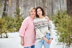 Madre e figlia adulta che camminano in precipitazioni nevose della foresta di inverno immagini stock libere da diritti