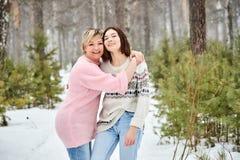 Madre e figlia adulta che camminano in precipitazioni nevose della foresta di inverno fotografia stock libera da diritti