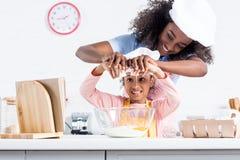 madre e figlia afroamericane sorridenti in cappelli del cuoco unico che un le uova nella ciotola immagini stock