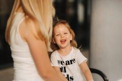 Madre e figlia all'aperto in città Gioco e divertiresi Divertiresi felice della figlia della madre e del bambino di modo fotografia stock