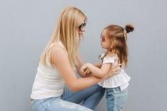Madre e figlia all'aperto in città Gioco e divertiresi Divertiresi felice della figlia della madre e del bambino di modo fotografie stock