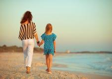 Madre e figlia alla moda sul litorale nella camminata di sera immagini stock libere da diritti