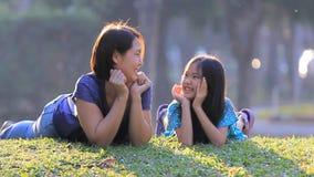 Madre e figlia asiatiche felici su erba al giorno di estate soleggiato in parco video d archivio
