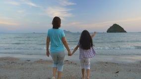 Madre e figlia asiatiche felici sulla vacanza alla spiaggia, movimento lento archivi video