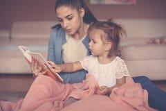 Madre e figlia a casa che si siedono sul pavimento e che leggono la BO fotografia stock libera da diritti