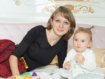 Madre e figlia caucasiche felici della famiglia sul letto a casa fotografie stock libere da diritti