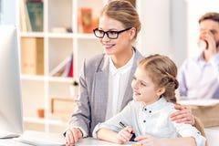 Madre e figlia che abbracciano e che considerano monitor nell'ufficio di affari, padre dietro fotografie stock libere da diritti