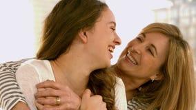 Madre e figlia che abbracciano sul sofà stock footage