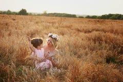 Madre e figlia che abbracciano sulla sua testa una ghirlanda delle rose, immagine morbida immagini stock