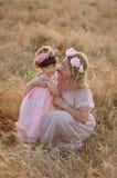 Madre e figlia che abbracciano sulla sua testa una ghirlanda delle rose, immagine morbida immagine stock