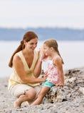 Madre e figlia che ascoltano il seashell alla spiaggia Fotografia Stock