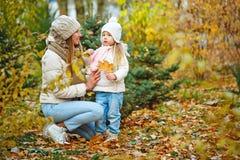 Madre e figlia che camminano nella sosta di autunno fotografie stock libere da diritti