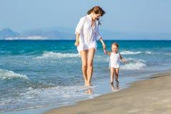 Madre e figlia che camminano sulla spiaggia Fotografia Stock