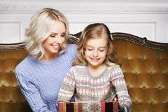 Madre e figlia che celebrano il Natale a casa Immagine Stock Libera da Diritti