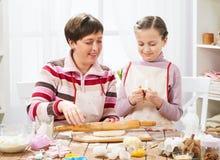 Madre e figlia che cucinano a casa, producendo la pasta per i panini Fotografia Stock