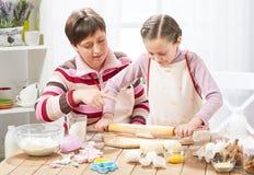 Madre e figlia che cucinano a casa, producendo la pasta per i panini Fotografia Stock Libera da Diritti