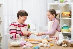 Madre e figlia che cucinano a casa, producendo la pasta per i panini Immagini Stock