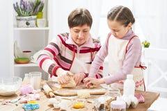 Madre e figlia che cucinano a casa, producendo la pasta per i panini Fotografie Stock Libere da Diritti
