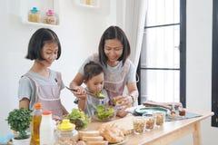 Madre e figlia che cucinano nella cucina a casa Fotografie Stock