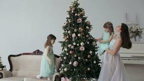 Madre e figlia che decorano l'albero del nuovo anno con i giocattoli archivi video