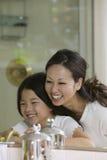Madre e figlia che esaminano riflessione in specchio del bagno immagini stock