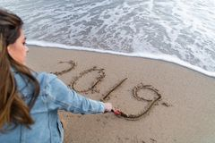 Madre e figlia che esaminano 2019 scritto sulla sabbia fotografia stock libera da diritti